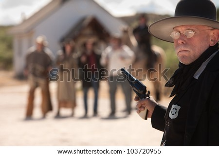 Outgunned sheriff in old American west showdown - stock photo