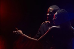 Outline of elegant African-American couple slowdancing together in dark, copy space