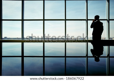 Outline of office worker speaking on the phone by the window