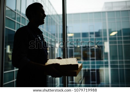 Outline of young courier carrying two boxes with pizza for clients to one of office in modern business center