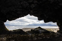 Outlines of an island inside the rock on Atlantic Ocean coastline, shore, where Basalt rock Hvitserkur is located, Iceland. View of the ocean and mountains through the hole in the rock. Island shape.