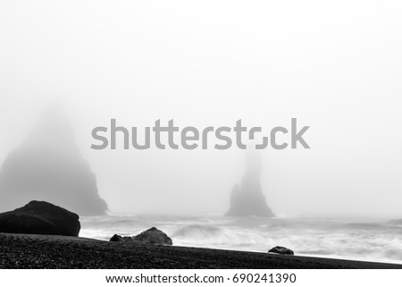Outlines of basalt sea stacks barely visible in the fog and wild sea spray - Reynisdragar, Iceland #690241390