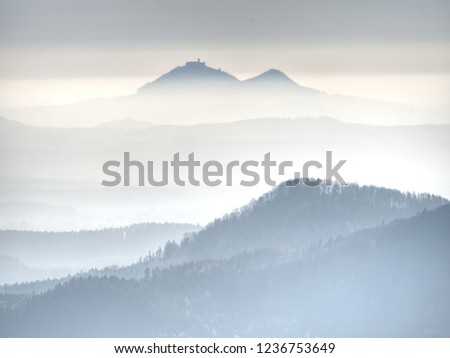 Outlines of forest hills hidden in thick mist.  Cold and damp morning in autumn nature. Unclear view to contours of hilly sides and peaks. #1236753649
