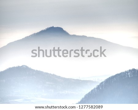 Outlines of forest hills hidden in thick mist.  Cold and damp morning in autumn nature. Unclear view to contours of hilly sides and peaks. #1277582089