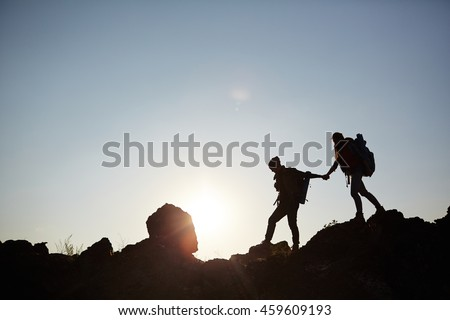 Outlines of two hikers crossing mountain