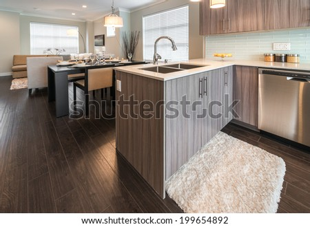 Outlook at the luxury modern kitchen with the living room at the back in a brand new house. Interior design.g