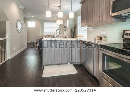 Outlook at the luxury modern kitchen with the living room at the back in a brand new house. Interior design.