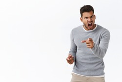 Outraged handsome man with bad temper losing control over emotions, distressed pointing camera and shouting accusations, blame someone in anger and furious feelings, standing white background