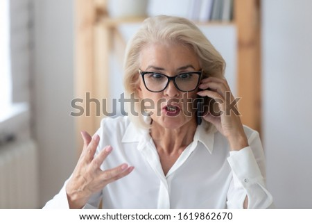 Outraged mature businesswoman talking by phone arguing with client feels irritated, 60s employee disputing having unpleasant conversation with customer, business problem solution, bad service concept Stock photo ©
