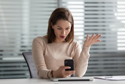 Outraged young female employee holding cellphone in hands, received bad news. Stressed manager annoyed by spam message, broken device, poor internet connection, discharged battery, bad working app.