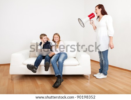 Outrageous mom screaming at kids with laptop using megaphone