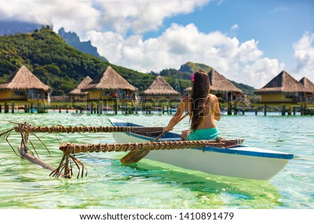 Outrigger Canoe - woman paddling in traditional French Polynesian Outrigger Canoe for recreational activity and watersport competition. Bora Bora with  overwater bungalow resort hotel sport lifestyle  #1410891479