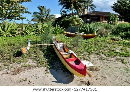 Outrigger Canoes resting on a shoreline property in Kauai Hawaii with a house in the background