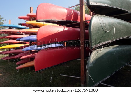 outside a water sports club, on giant shelves, multicolored canoes are stacked one above the other