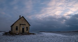 Outside of a dilapidated yellow-brick one-room school house located on the open Canadian prairie.  Picture taken at dusk with white and blue-grey clouds and a hint of pink. Snow on the field.