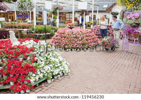 Outside of garden center with many types of plants and flowers and couple pushing a trolley