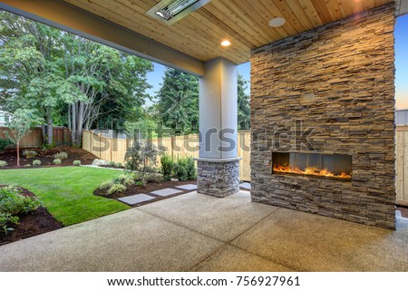Outside Patio features natural wood plank ceiling, concrete floor and oversized stone fireplace overlooking a beautiful expansive yard.  Northwest, USA