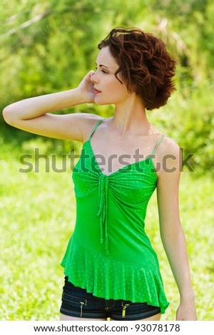 outside portrait of beautiful young curly woman talking over mobile phone in park