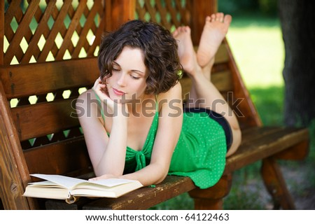 outside portrait of young beautiful curly woman laying on bench and reading book in park