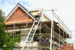 Outside renovation of modern residential house, scaffolding tower