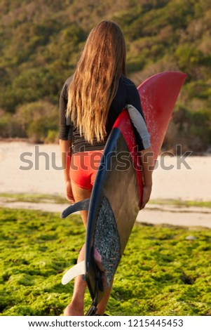 Outside shot of beautiful woman with long straight hair, likes extreme sport, carries surfboard, has surfer lifestyle, being in good body shape, walks on coast alone. Outdoor active hobby concept