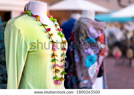 Outside store street in New Mexico city with blurry background and foreground closeup of green clothing dress shirt with colorful handmade necklace on mannequin