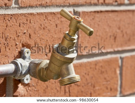 Outside tap on brick wall