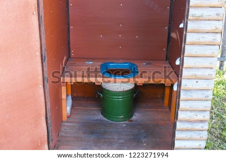 Outside toilet with a pot in village.