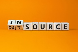 Outsource or insource symbol. Fliped wooden cubes and changed the word 'outsource' to 'insource'. Beautiful orange background, copy space. Business and outsource or insource concept.