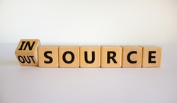Outsource or insource symbol. Fliped wooden cubes and changed the word 'outsource' to 'insource'. Beautiful white background, copy space. Business and outsource or insource concept.
