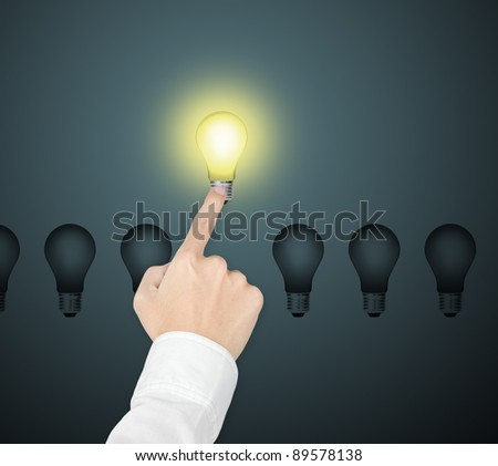 outstanding bright light bulb symbol of leading idea being pointed by male hand