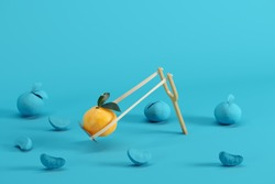 Outstanding mandarin orange in a slingshot surrounded by oranges painted in blue on blue background. Minimal fruit idea concept.