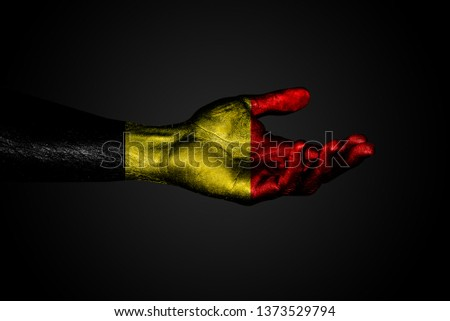 Outstretched hand with a drawn Belgium flag, a sign of help or a request, on a dark background. Horizontal frame #1373529794