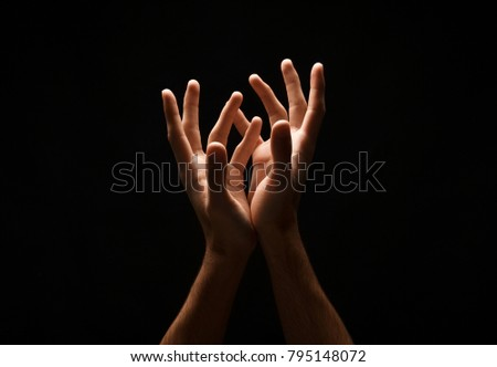 Outstretched male hands, man keeping empty cupped palms together isolated on studio black background - concept of charity, support, protection and care, closeup, copy space, cutout #795148072