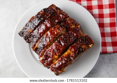 Oven-baked barbecue ribs with sauce on a white plate with a red checkered picnic napkin for a family barbecue Foto stock ©