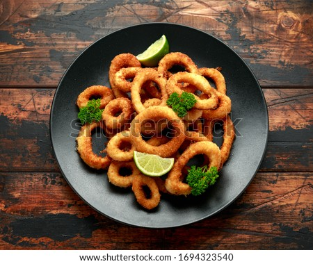 Oven baked breaded calamari rings served with lime wedges, sweet chilli sauce and mayonnaise Сток-фото ©