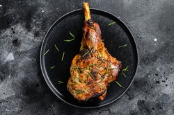 Oven baked lamb leg. Dark background. Top view