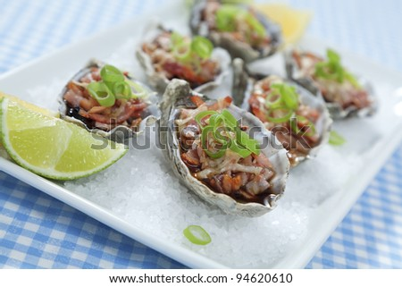 Oven baked oysters kilpatrick on a bed of rocksalt with lemon and lime