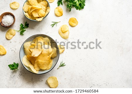 Oven baked  potato chips in bowls. Homemade crispy potato chips on white background, top view, copy space. Foto stock ©