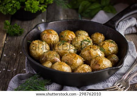 Oven Baked potatoes with herbs on cast iron pan, selective focus