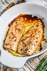 Oven Baked salmon or trout fillet. White woodenbackground. Top view
