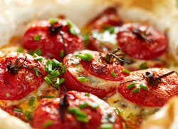 Oven baked tomatoes stuffed with spinach, cheese and herbs, close up. Delicious and nutritious vegetarian meal