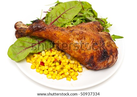 Oven baked turkey leg served with salad and corn, isolated on white. - stock photo