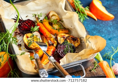Oven Roasted vegetables with garlic and herbs on the baking tray. Autumn-winter root vegetables. #712757182