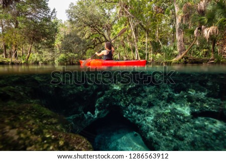 Over and Under picture of a girl kayaking in a lake near an underwater cave formation. Taken in 7 Sisters Springs, Chassahowitzka River, Florida, United States of America.