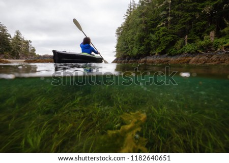 Over and Under picture of anAdventurous woman kayaking in the Pacific Ocean during a cloudy morning. Taken in Port Hardy, Vancouver Island, BC, Canada.