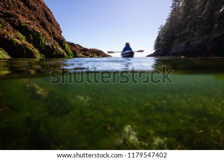 Over and Under picture of anAdventurous woman kayaking in the Pacific Ocean during a sunny morning. Taken in Port Hardy, Vancouver Island, BC, Canada.