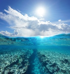 Over and under water surface seascape, sunlight with cloudy blue sky and split by waterline a natural trench in the reef underwater, Pacific ocean, French Polynesia