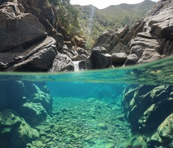 Over and underwater split view in a river with clear water and big rocks, New Caledonia, Dumbea river