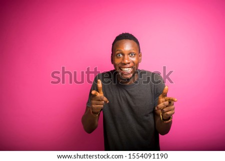 over excited young african man pointing at the camera doing a funny face . reaction concept